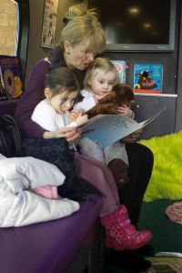 Mother reading to child on book bus